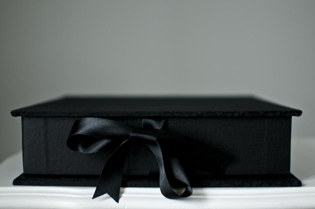 Black brocade. 10 inch square format with ribbon tie closures.